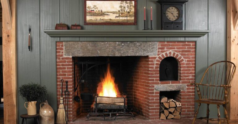 A glowing fire in a huge brick fireplace with big granite lintel stone and beehive oven