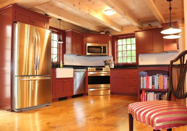 View of country kitchen with timbered ceiling and wide board floors.