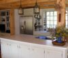 Antique kitchen with white cabinets and timbered ceiling.