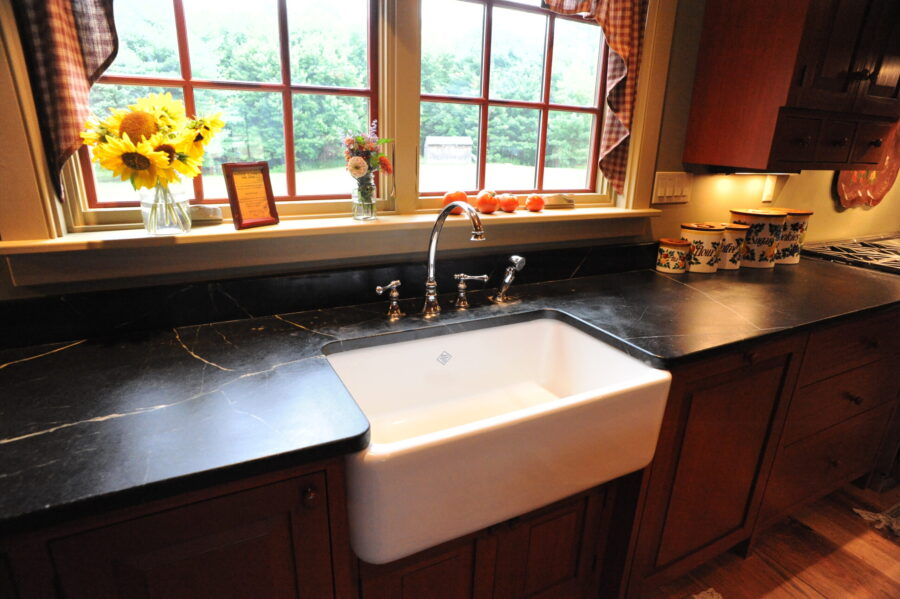 A deep white porcelin farmhouse sink inset in black soapstone counters.